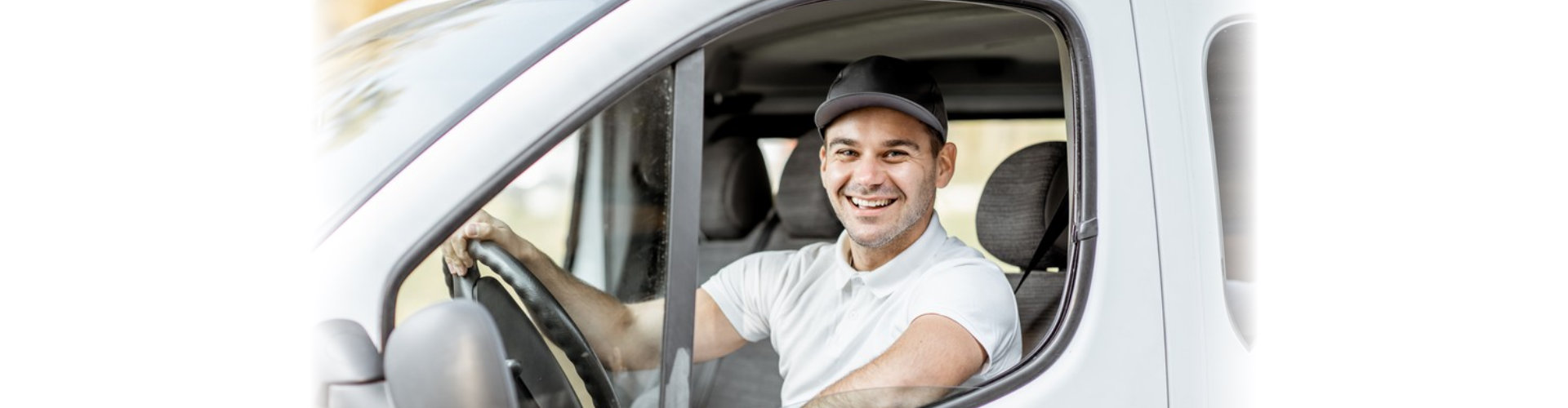 Portrait of a cheerful delivery driver in uniform looking out the window