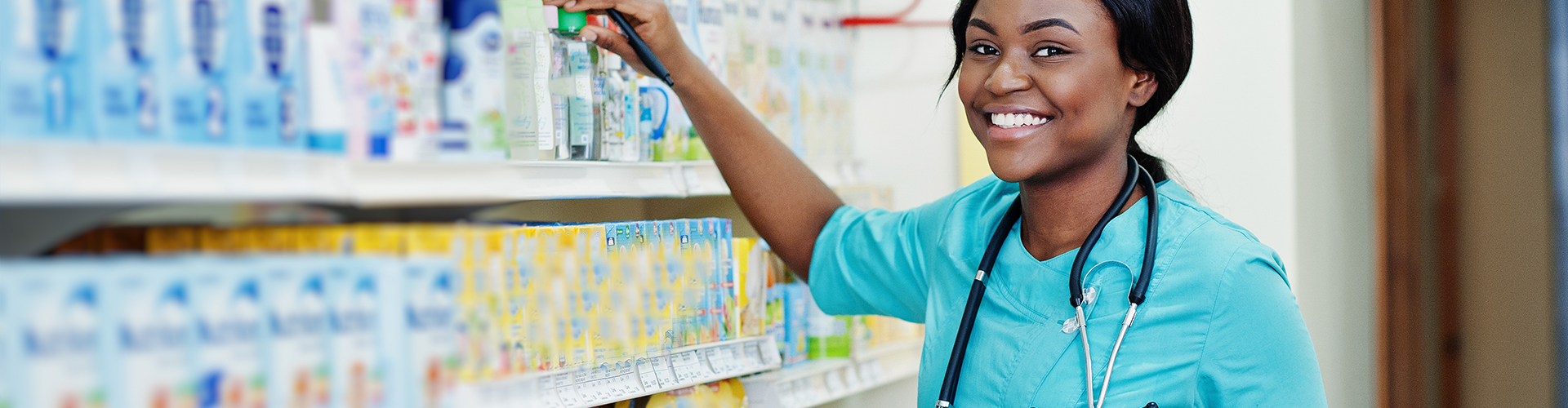 pharmacist smiling while taking medicine from shelf